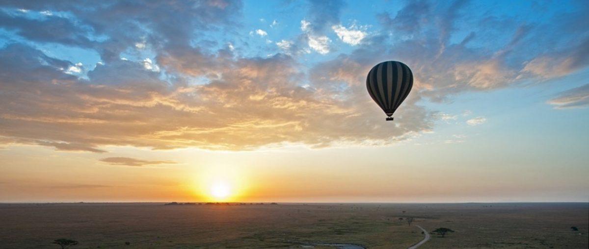 Ballon vor Sonne welche knapp über einem weitem flachen Horizont steht